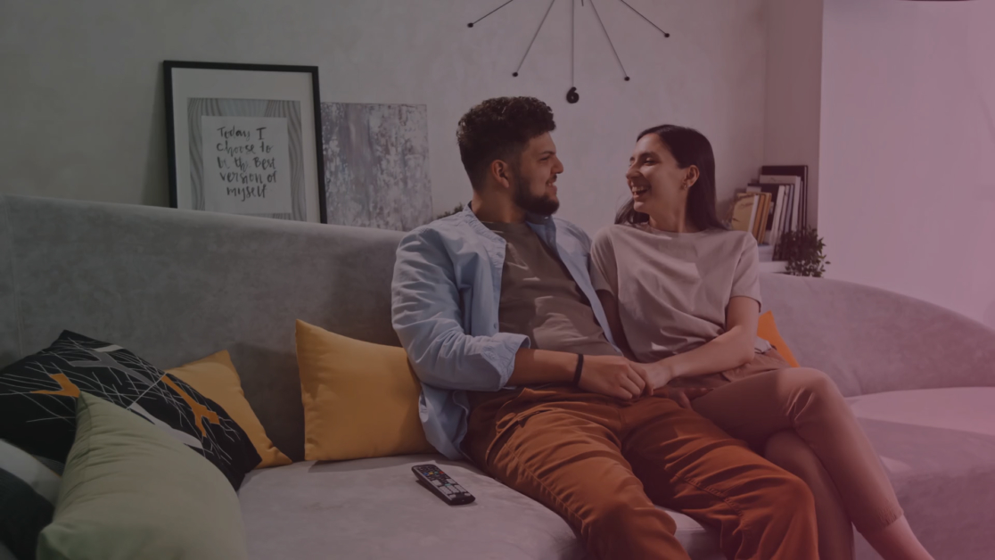 medium pan shot of happy young latin couple sitting on sofa in modern living room a SBV HD